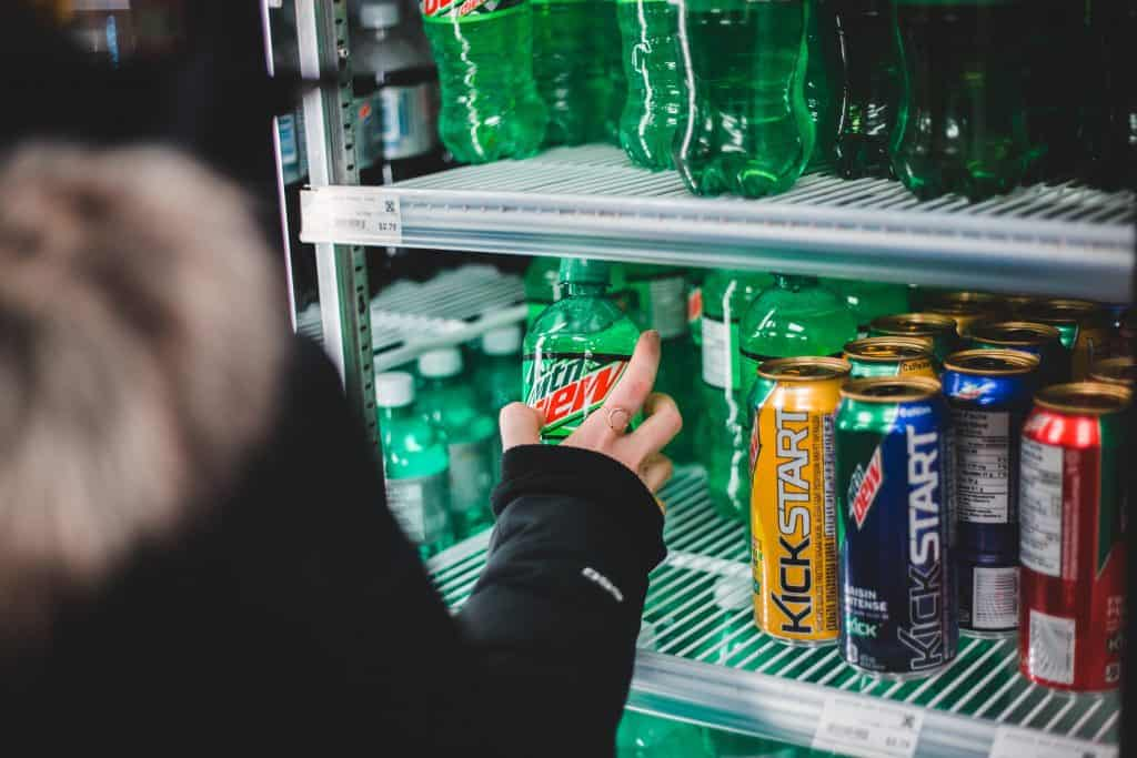 person holding sprite and orange soda cans