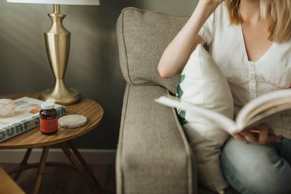 woman sitting on sofa holding book
