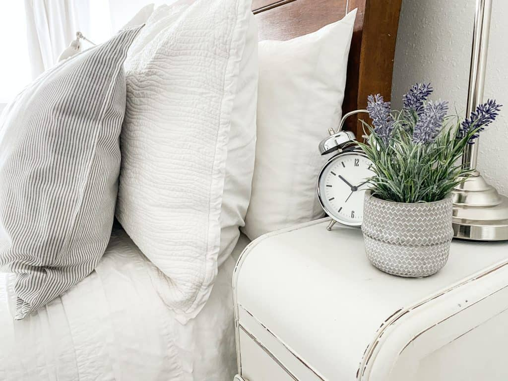 white and silver analog alarm clock on white couch