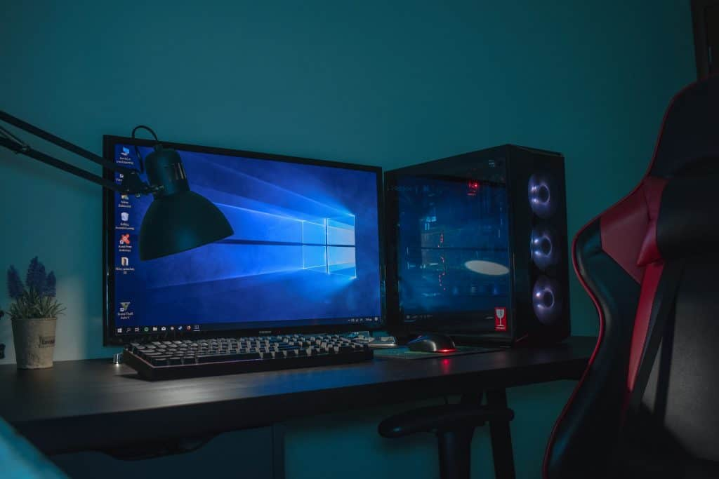 turned on desktop computer set with black and gray leather gaming chair