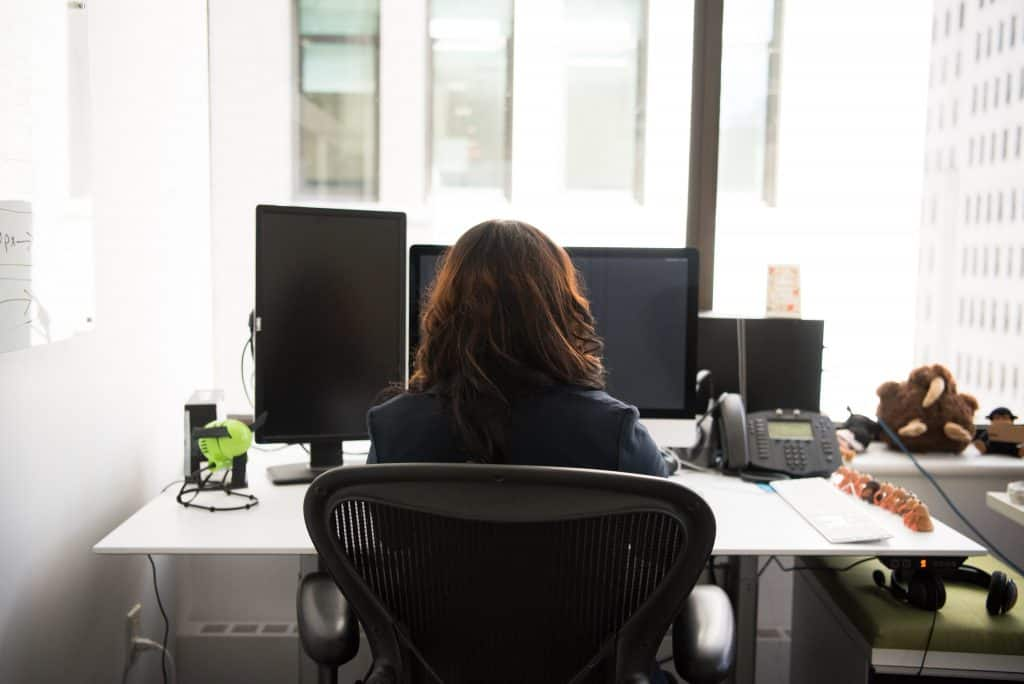 woman sitting on chair front of desk with desktop